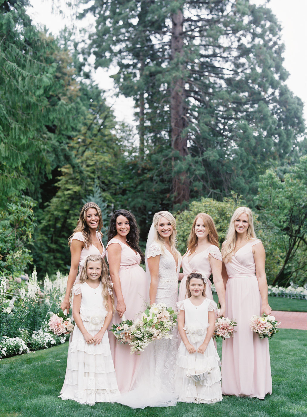 Sweet bridal party with flower girls holding cream and blush bouquets.