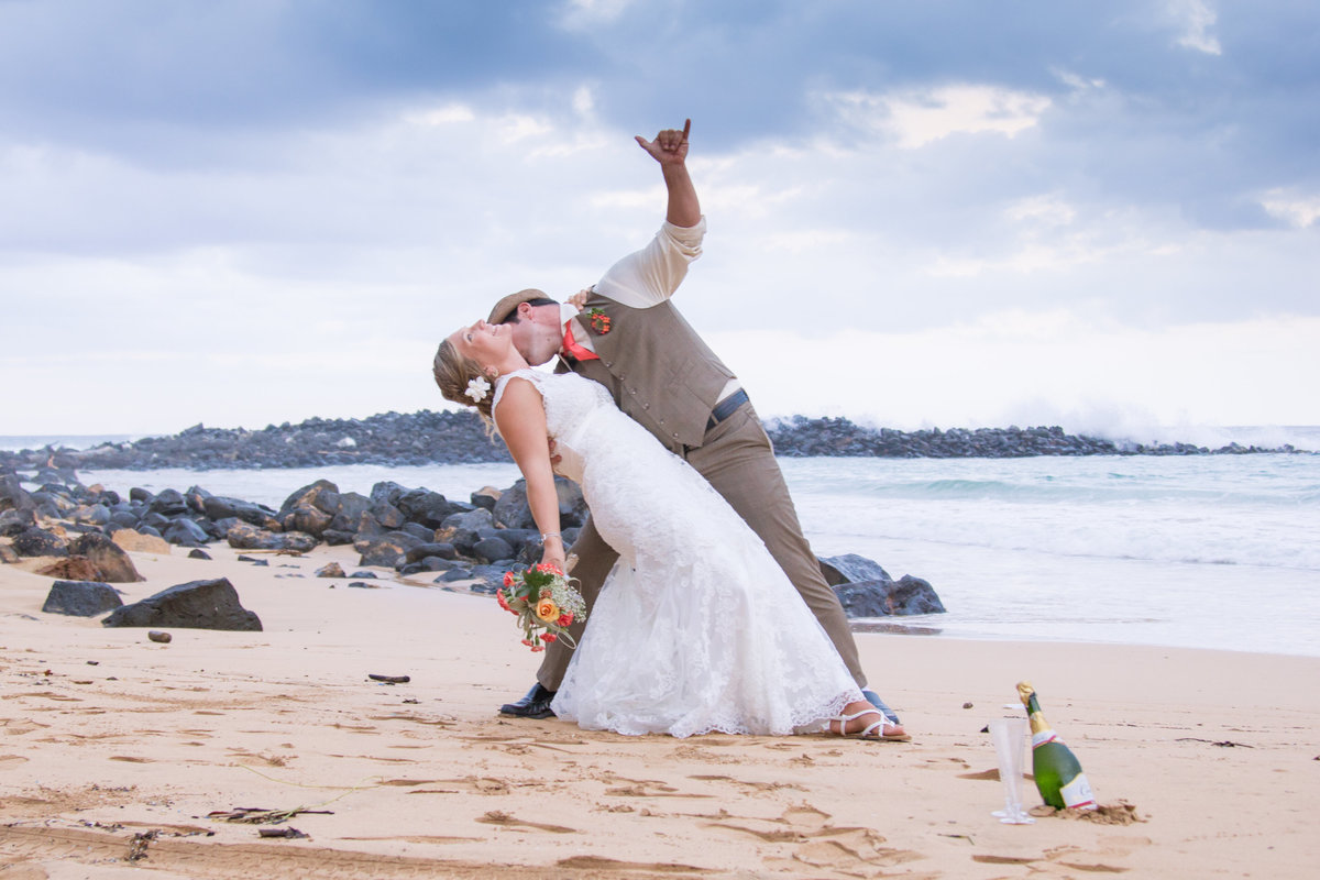 Groom gives a shaka as he dips his  bride with champagne on the sand at a Kauai beach wedding.