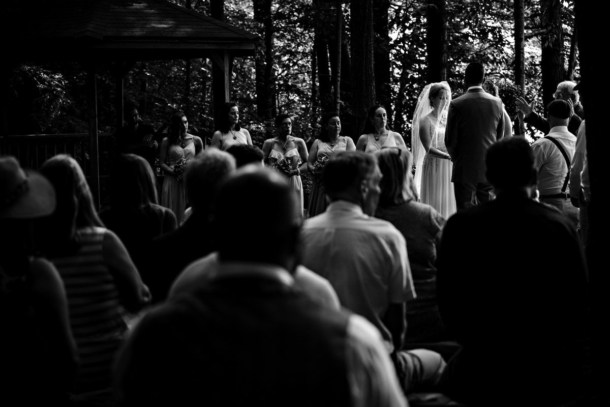 Dublin New Hampshire wedding ceremony in the woods with sun peeking through past Mount Monadnock at their camp wedding