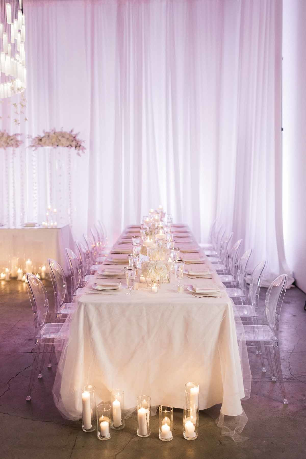 These beautiful long white tables with ghost chairs designed by Flora Nova Design make for a stunning wedding reception.