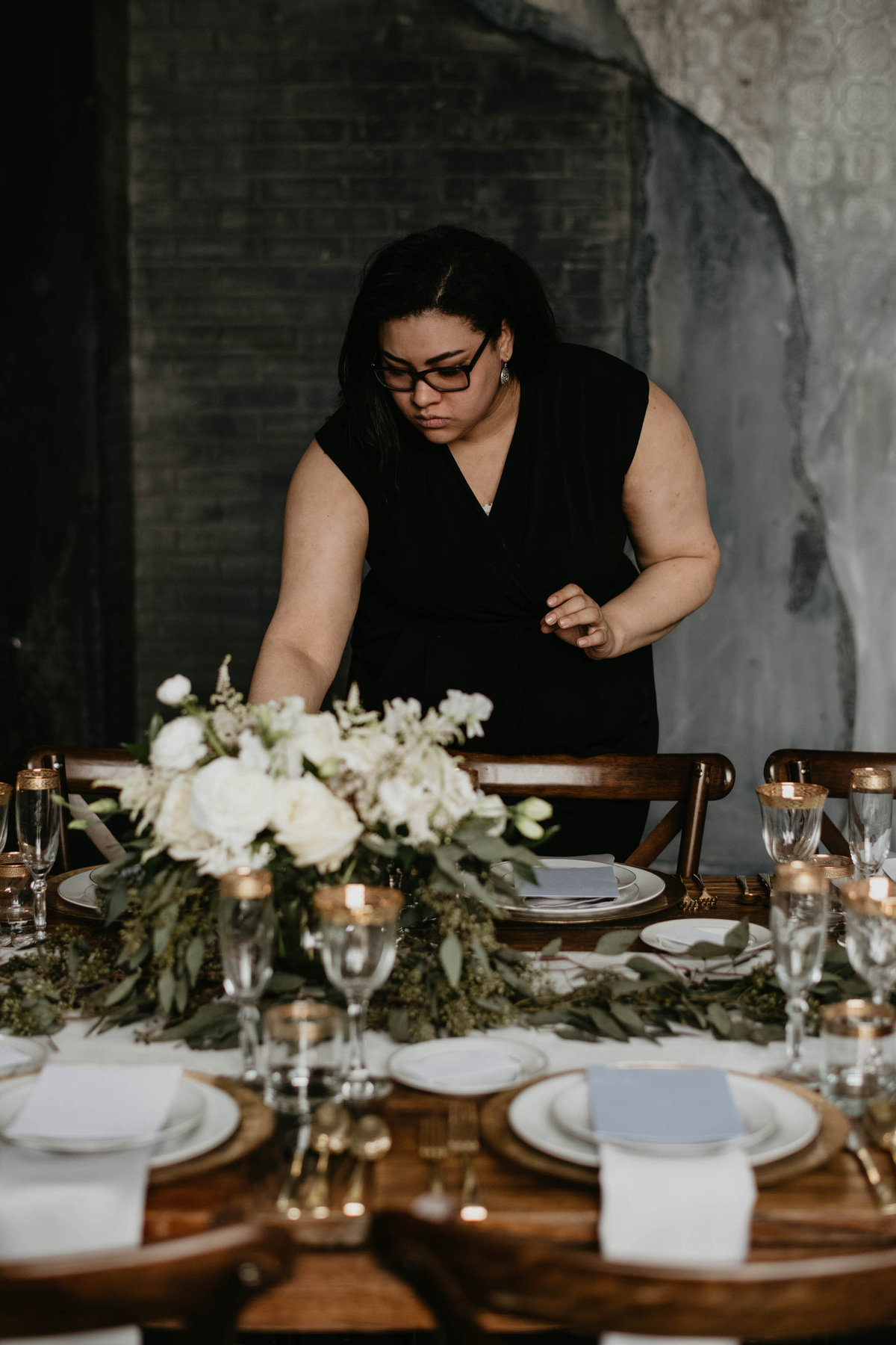 wedding planner sets elaborate table with gold plates, and harvest table