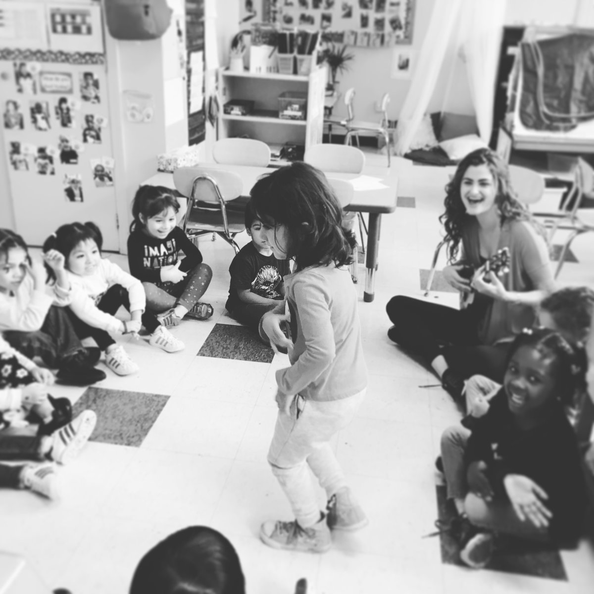 Laura Volpacchio plays ukulele while teaching a dance class as preschooler dances alone surrounded by her peers