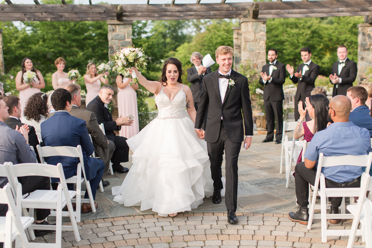 bride and groom coming down the aisle at lewis ginter botanical garden