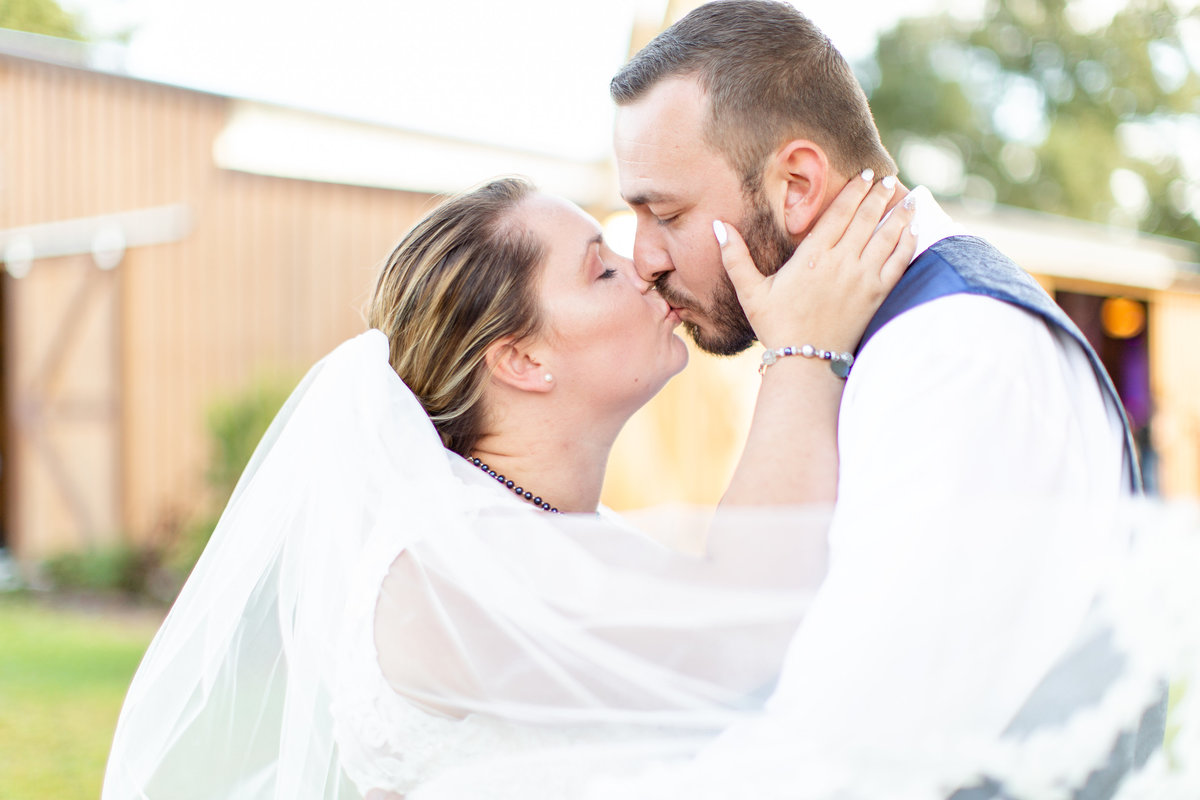 Bride and groom kiss on their wedding day in front of barn wedding venue with her white bridal veil blowing in the wind to create a romantic wedding photo in Lakeland, Florida