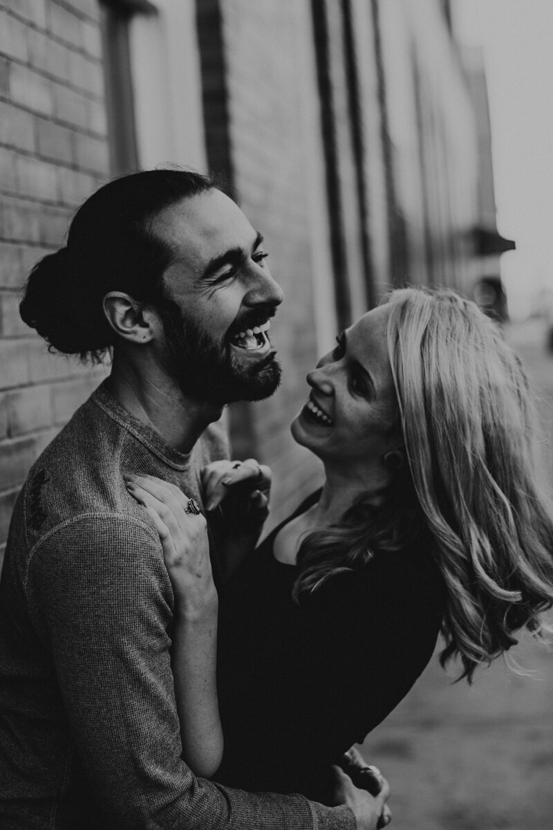 engaged couple holding each other laughing downtown