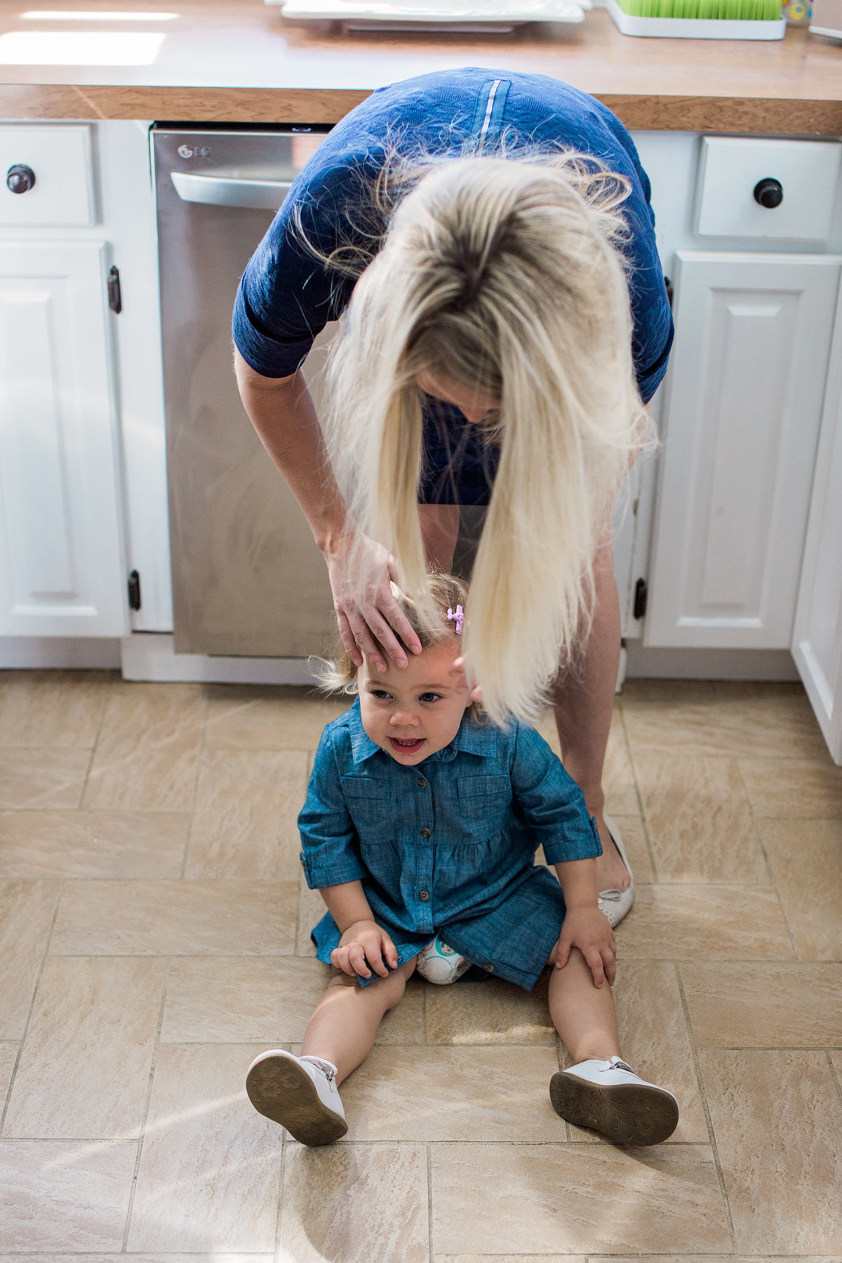 Mom fixing little girls hair during lifestyle family session with Jennifer Blaak Photography