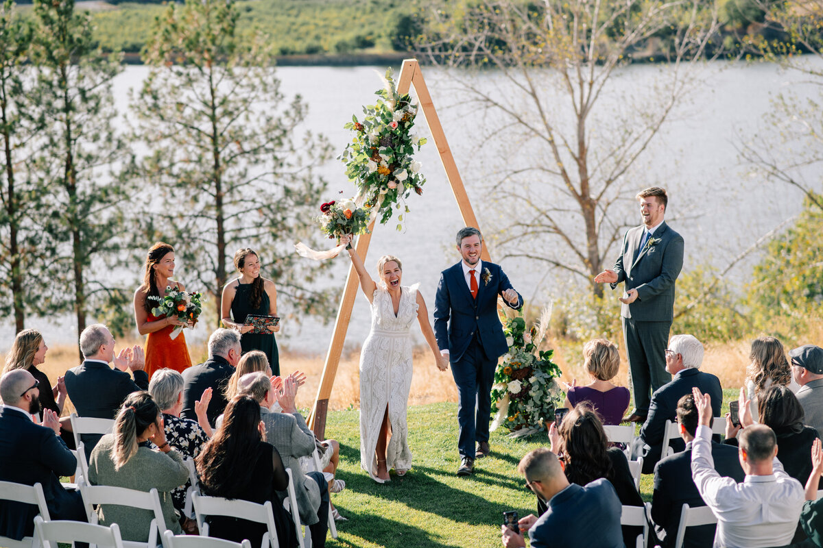 Couple and guests cheering after intimate Lake Chelan fall wedding ceremony