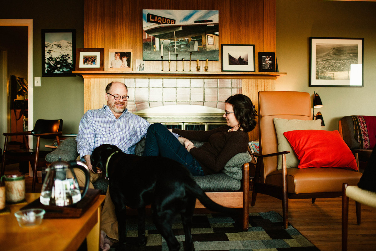 husband and wife sitting on couch in midcentury modern living room