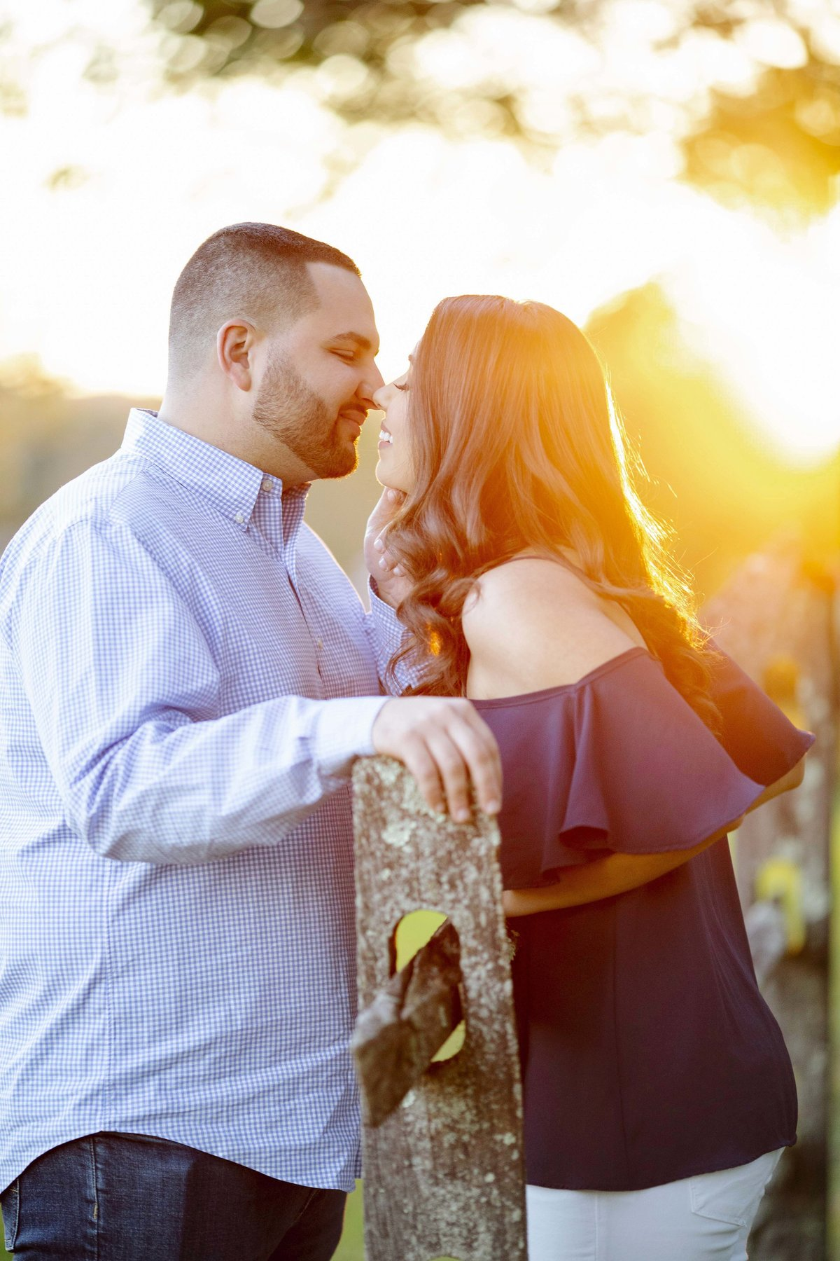 engaged couple kissing by fence at  bayonet farm