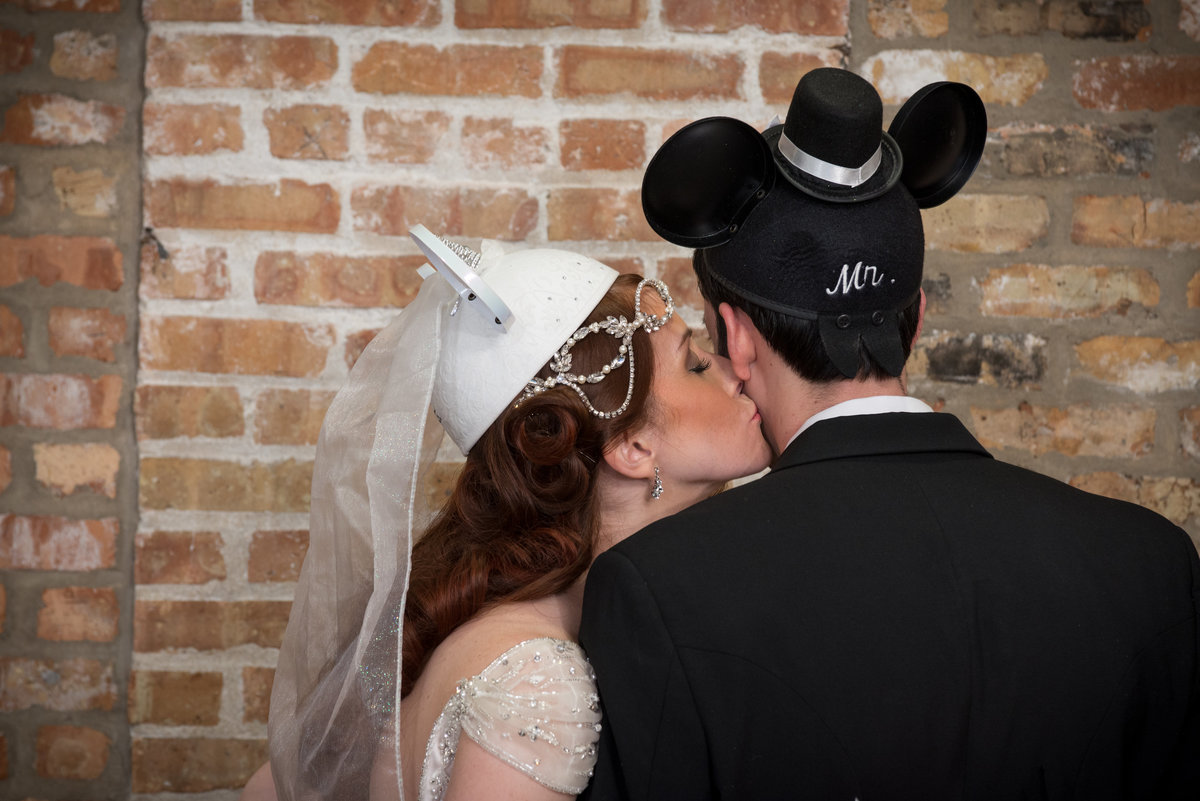 Bride kissing groom with wedding mickey mouse ear hats on