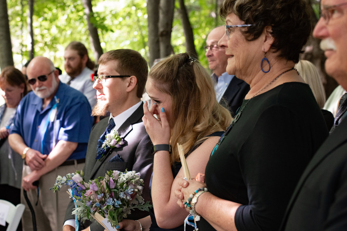 guest cries at ceremony wipes tear
