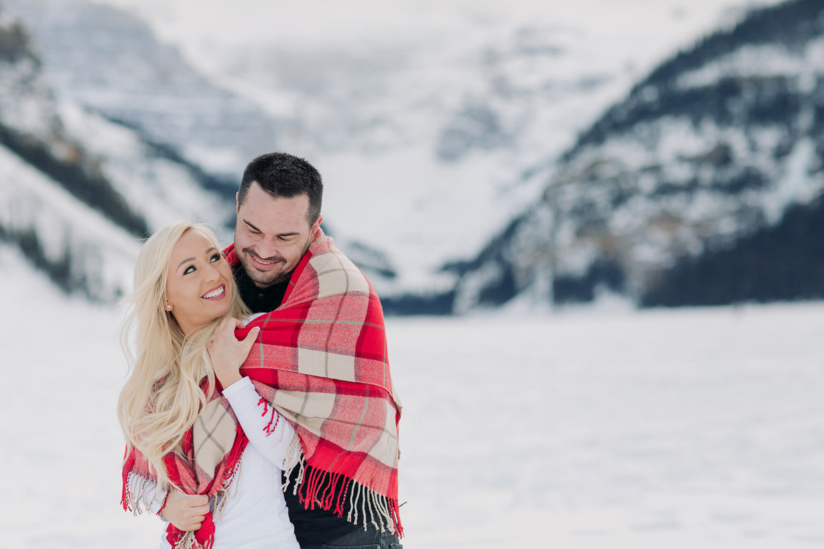 lake louise winter couples photos cuddle red plaid blanket