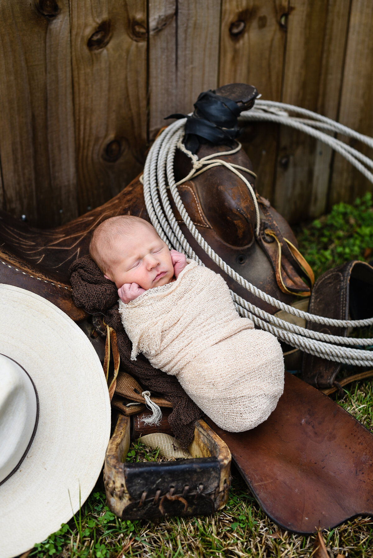 Beautiful lifestyle newborn photography: newborn boy lays in his dad's saddle with cowboy hat nearby in Mississippi