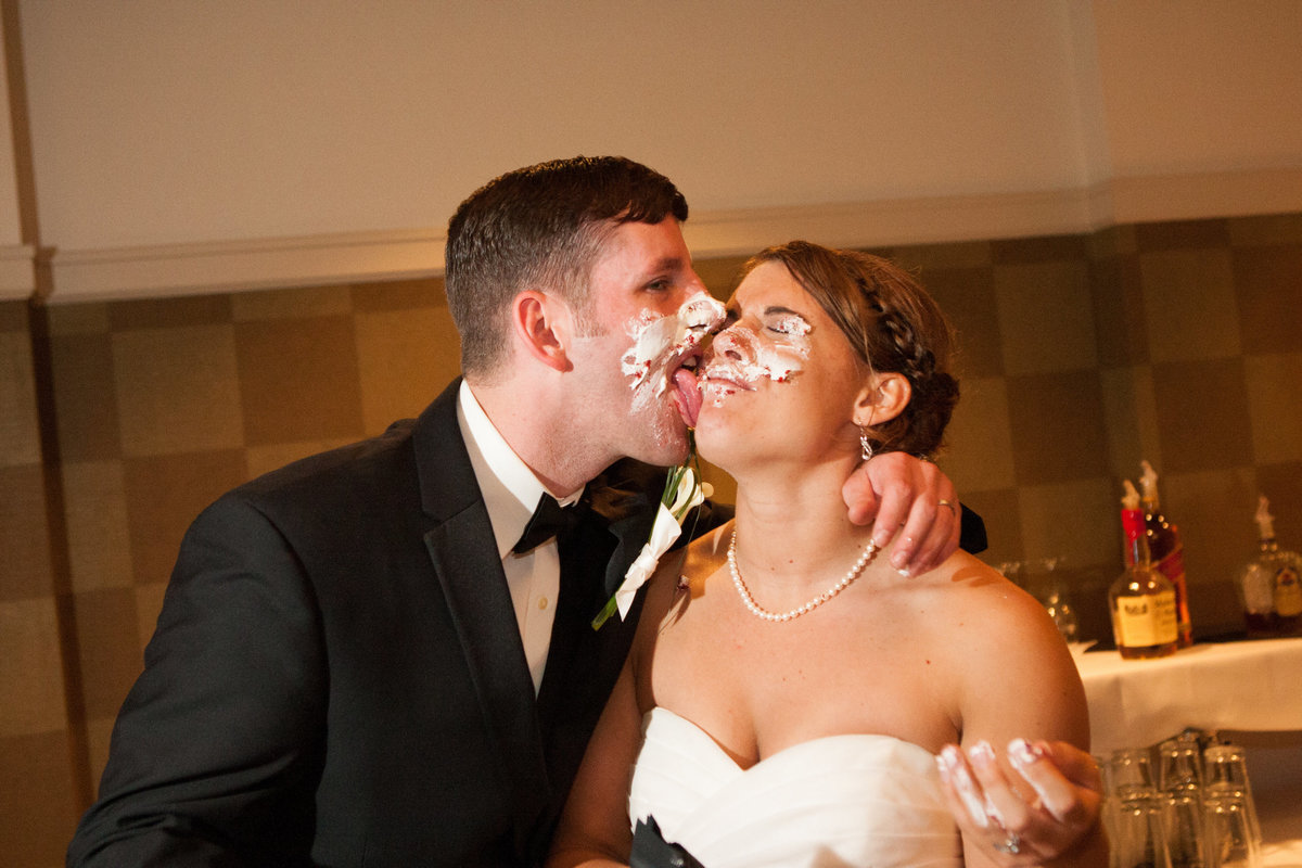 Groom eating cake off bride