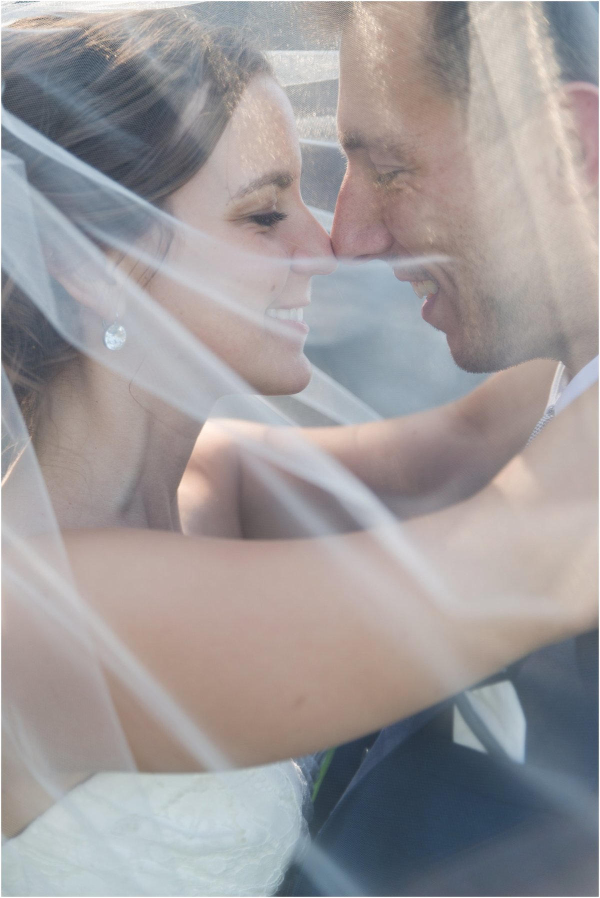 Bride & groom touching noses, veil