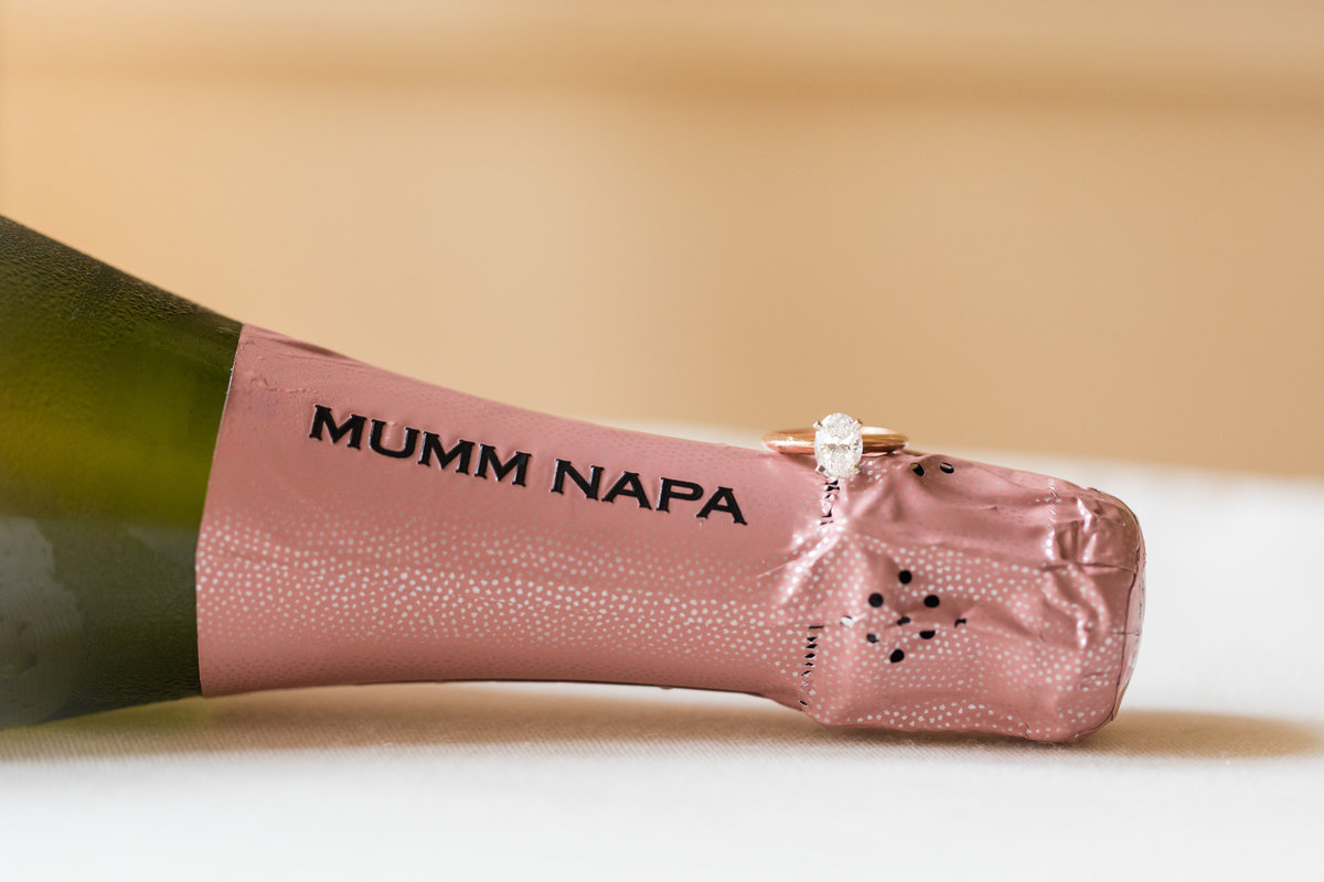 Wedding ring rests on the top of a Mumm Napa Champagne bottle