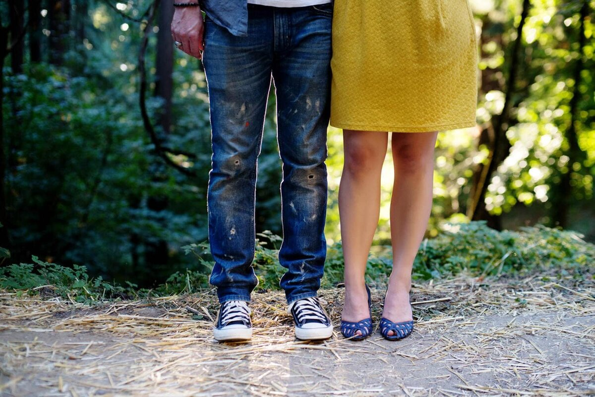 from the waist down, a woman is wearing a bright yellow skirt and blue shoes and a man wears paint covered jeans and converse