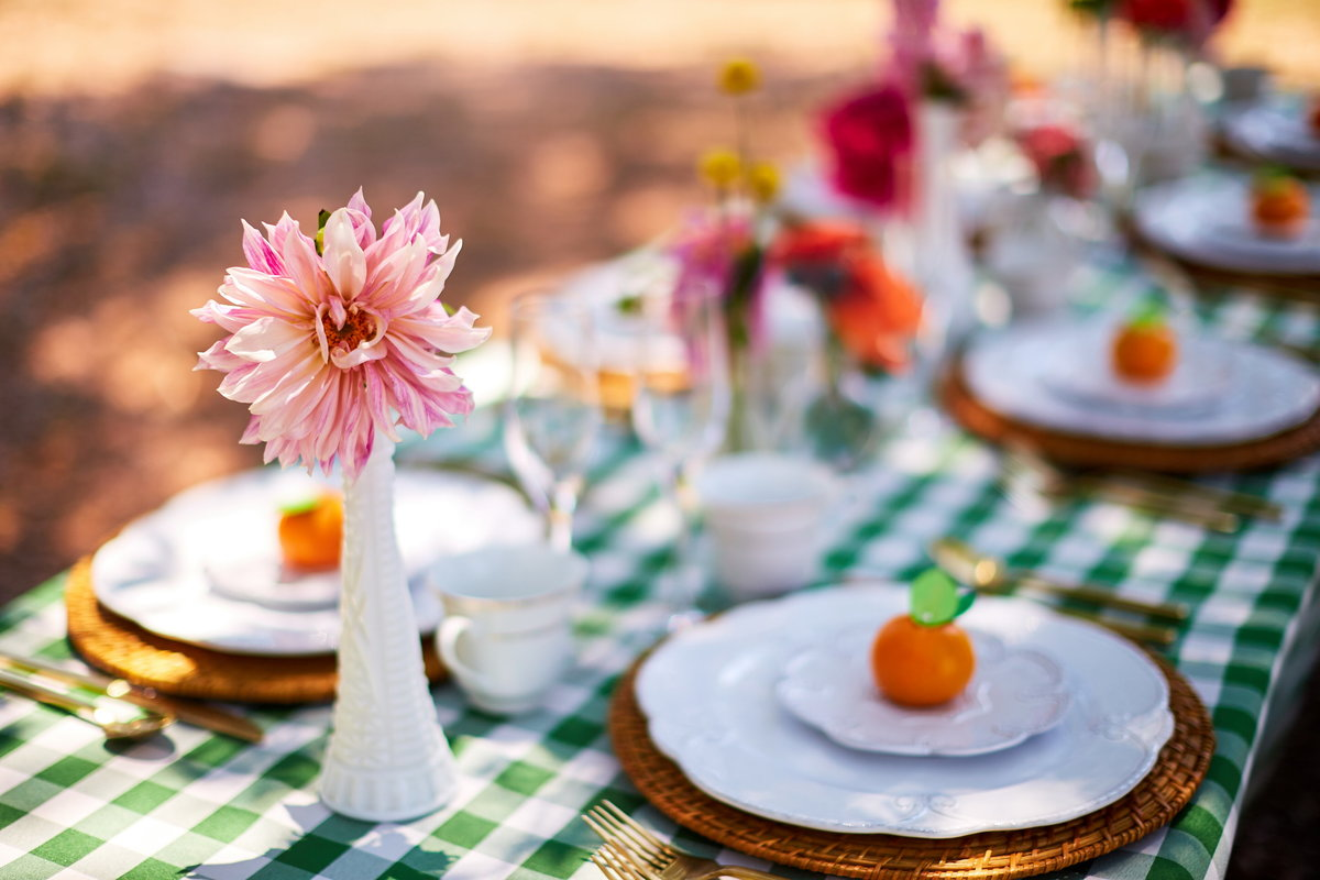 Colorful, gingham outdoor reception table and floral decorations at Charleston Woodlands, SC
