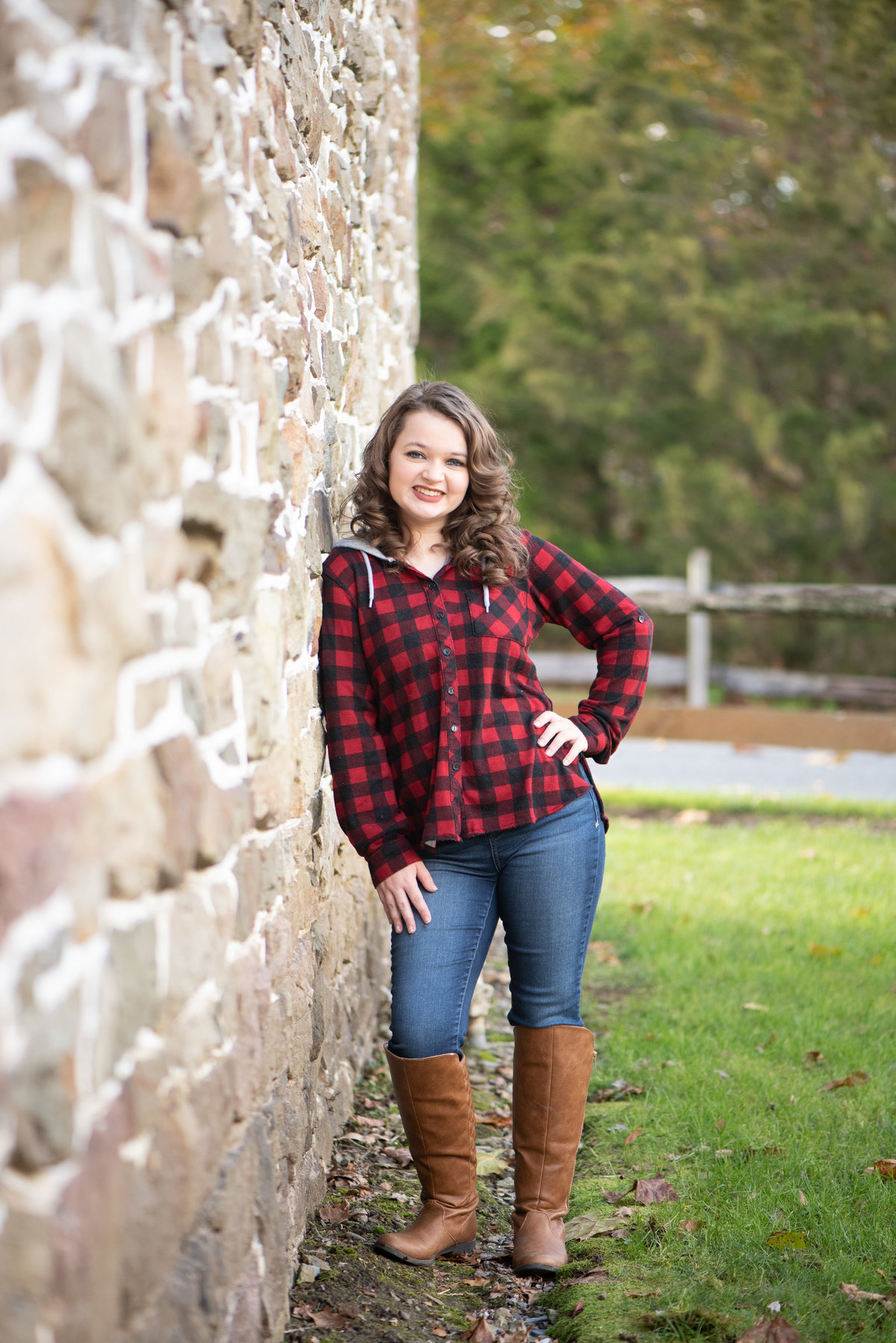 High School Senior Girl in buffalo plaid leaning against stone wall