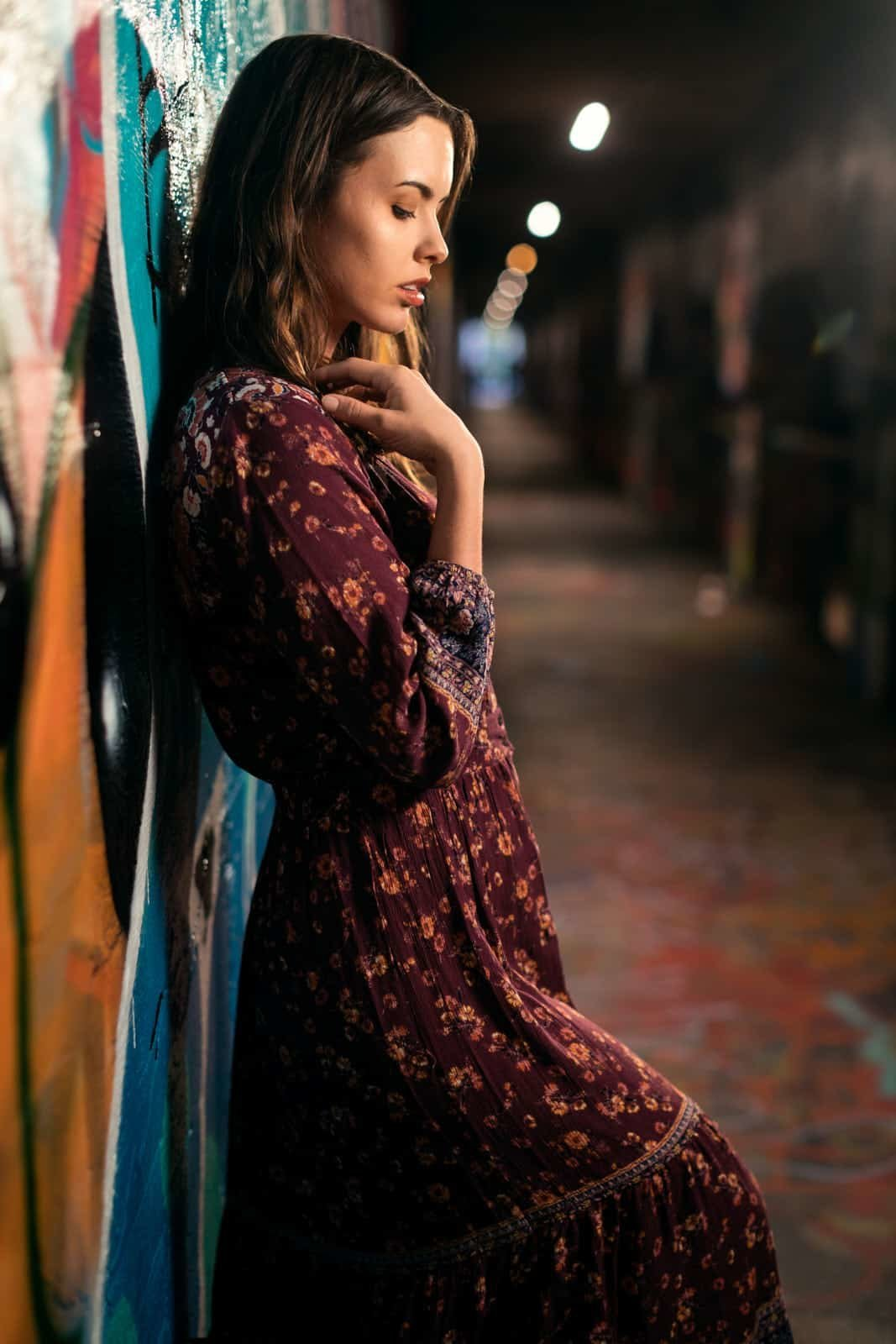 floral dress girl leans against graffiti wall of Krog Street Tunnel Atlanta