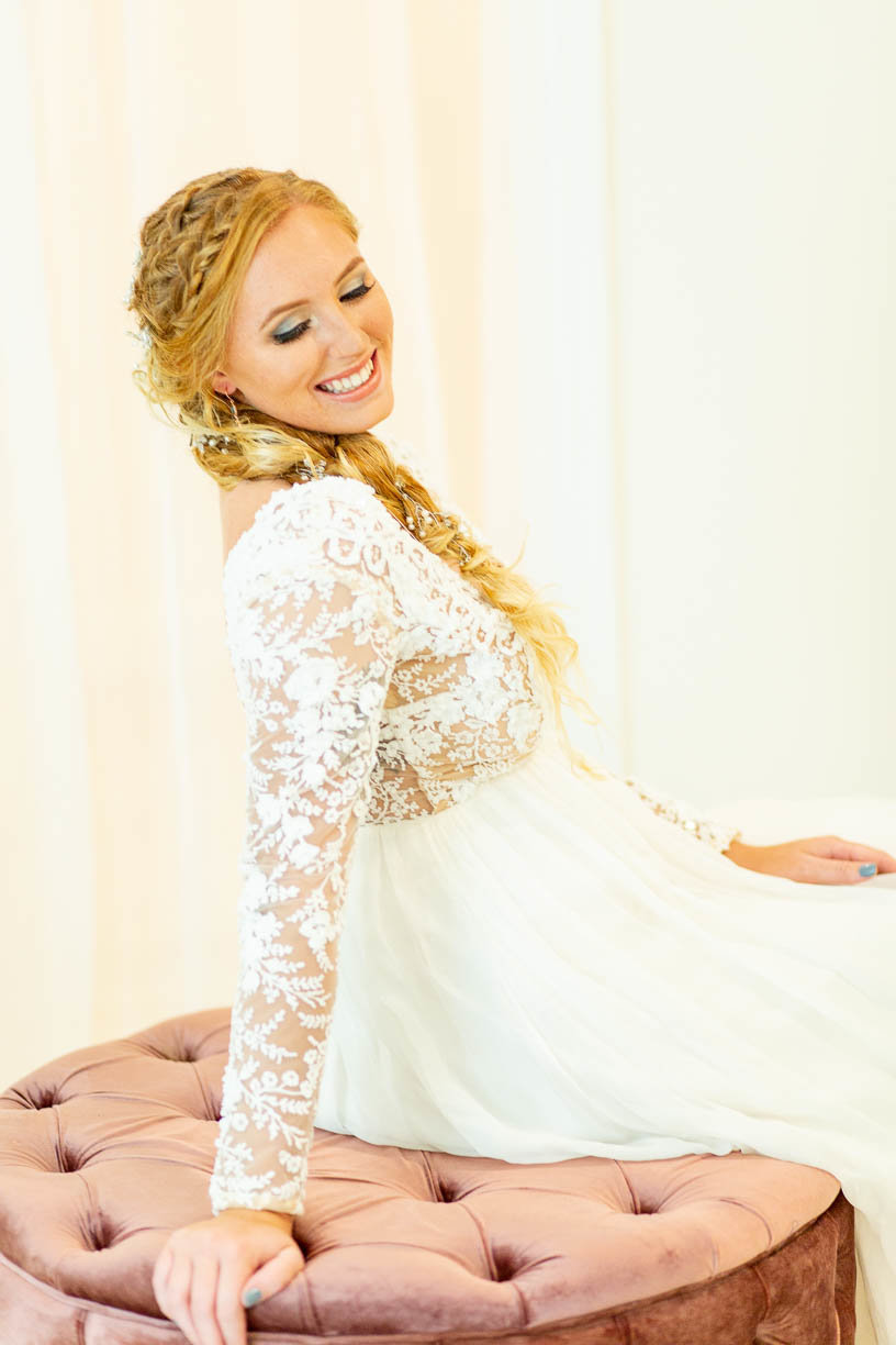 Bride with long braid hairstyle in long sleeve wedding dress smiles for a photos while she is getting ready on the morning of her wedding day