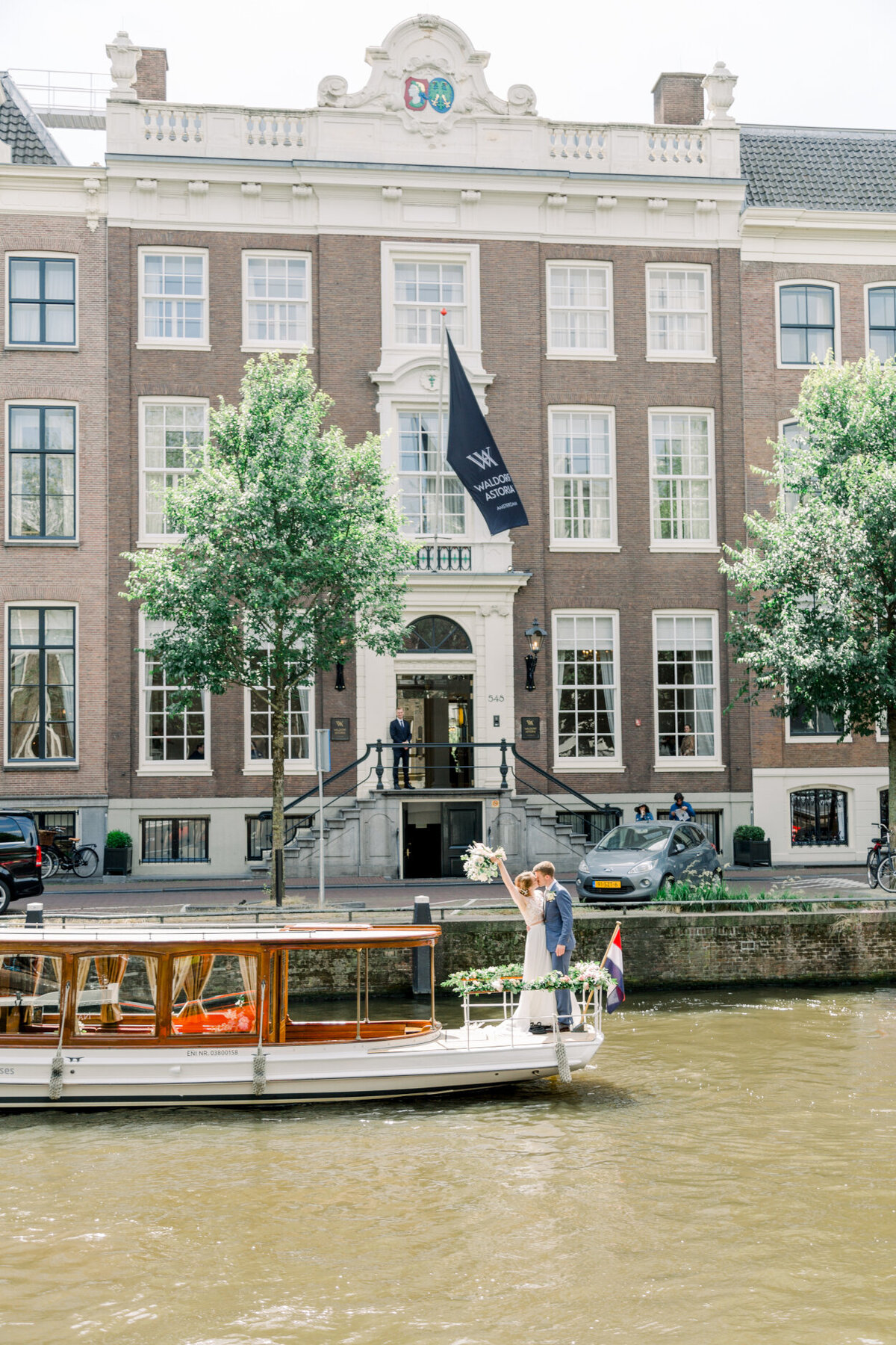 Wedding couple celebrating their wedding on a canal boat tour in Amsterdam for a photo shoot organized by Lovely & Planned