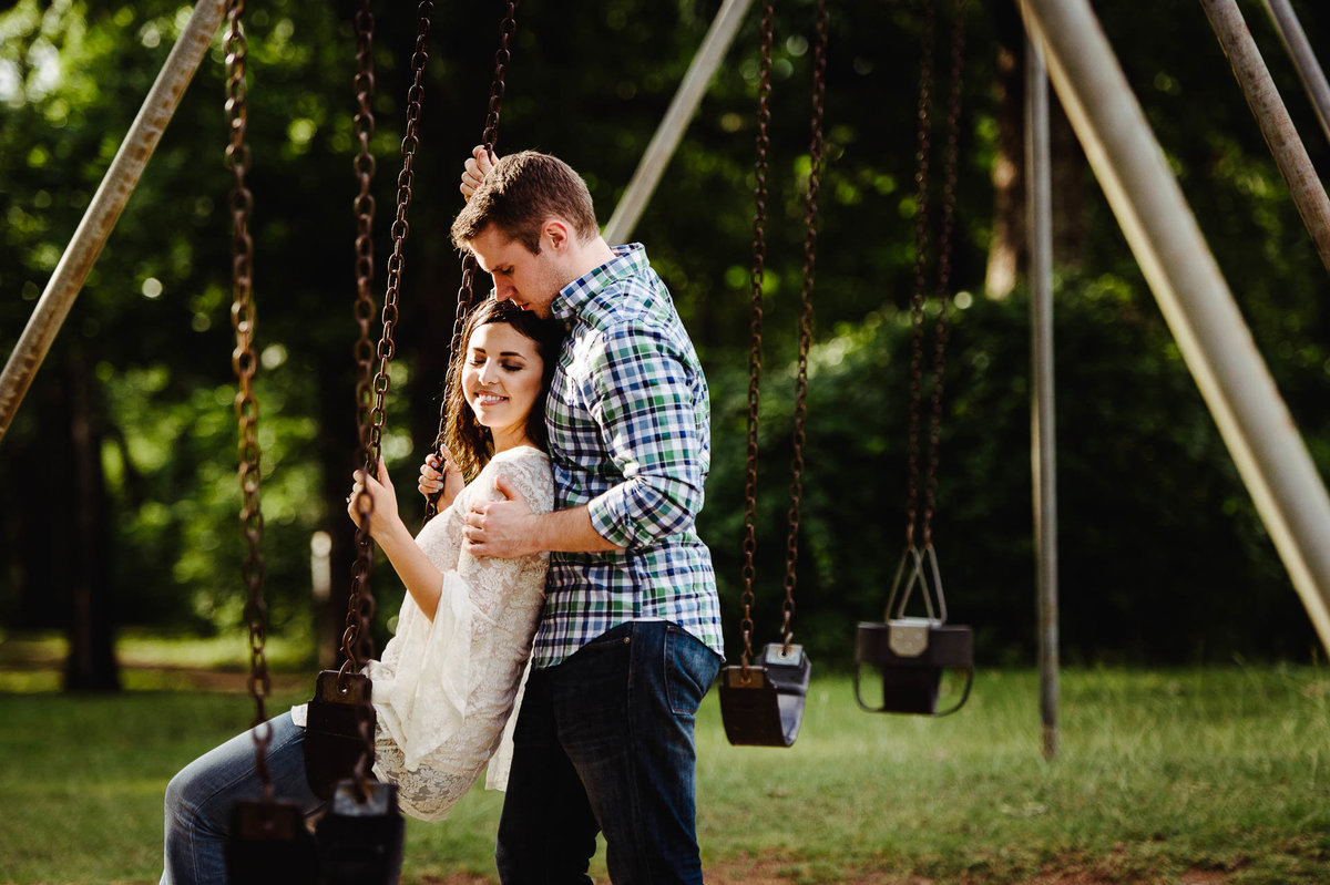 couple on swing at white rock lake for their dallas engagement session