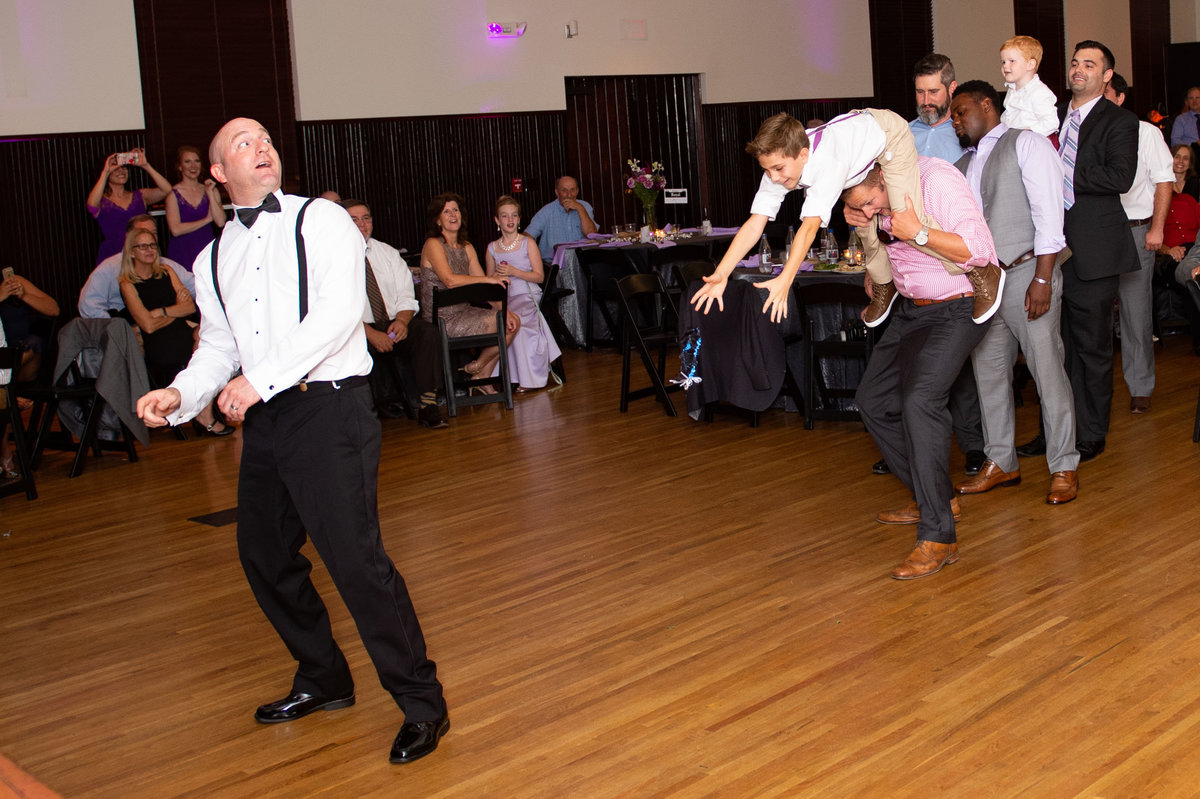 boy on fathers shoulders almost falls catching garter