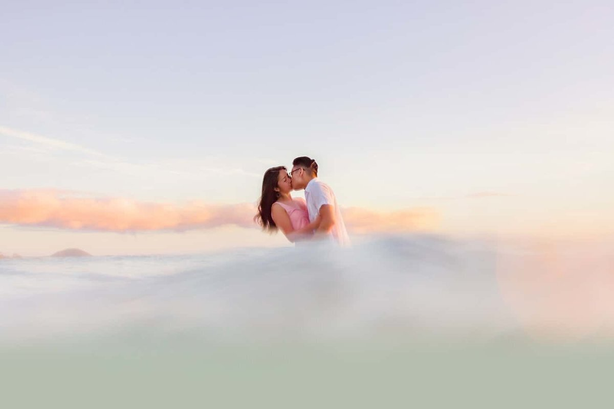 Sunset engagement portrait of couple kissing in the ocean on Maui
