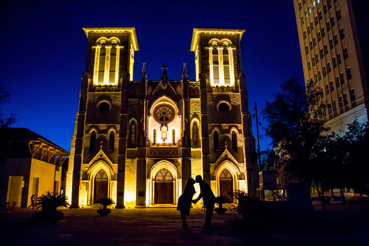 Silhouette of engaged couple kissing in front the San Fernando Cathedral in San Antonio in the Main Plaza at night.