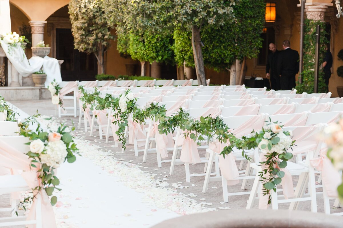 ceremony-setting-with-blush-chair-sashes-and-greenery