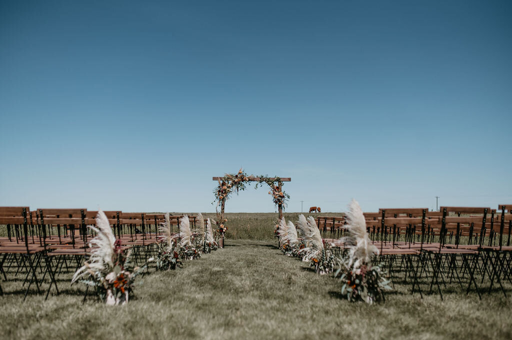 wooden chairs located in a field with a wood arbor and florals lining the aisle