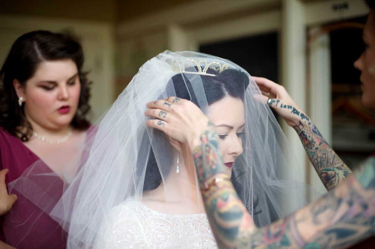 a bridesmaid with tattoo sleeves helps the bride put on her vintage veil