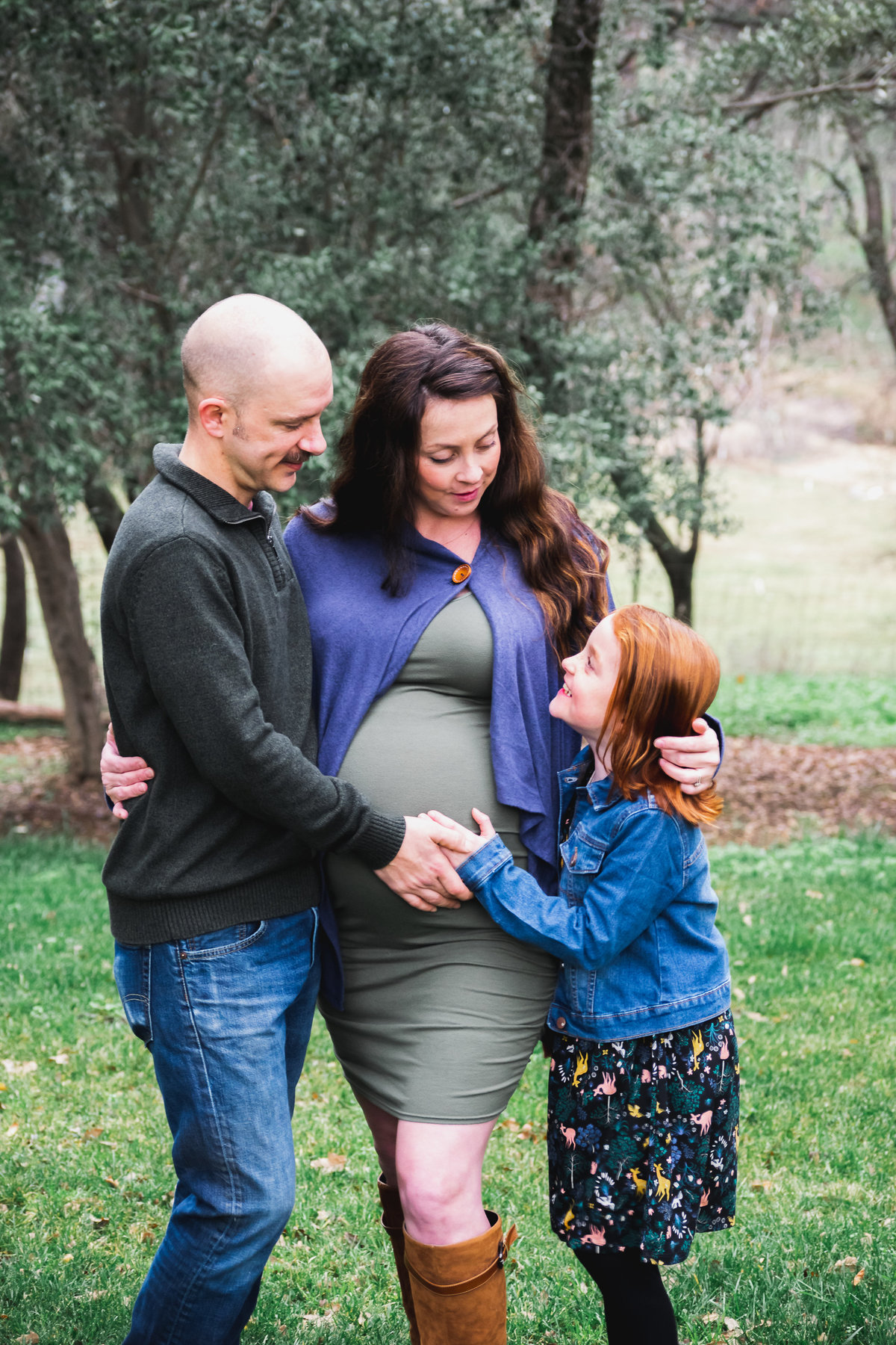 family maternity portrait of mom, dad and young girl in grassy field
