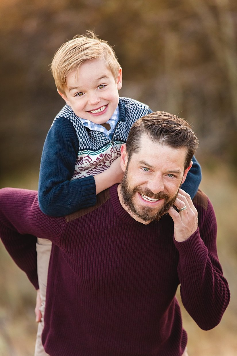 A father and son dressed in burgundy and blue with his cute little boy on his back.