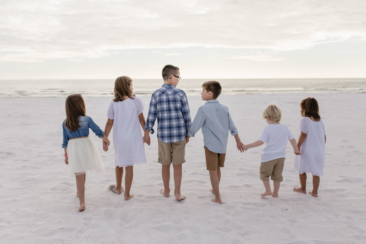 6 cousins holding hands and walking during family session