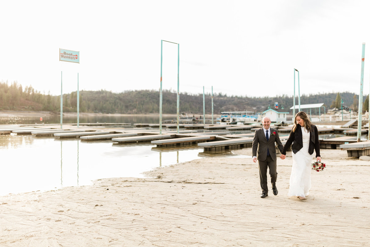 newlywed couple walking along the shores of bass lake in the winter