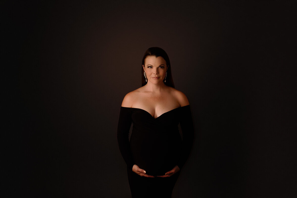 Pregnant woman in black dress holding Belly