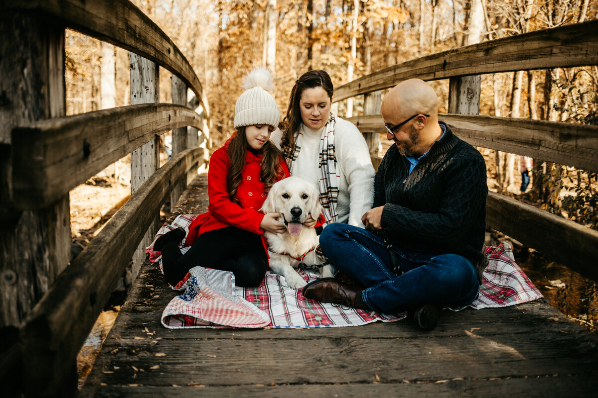 Family snuggling with dog on bridge