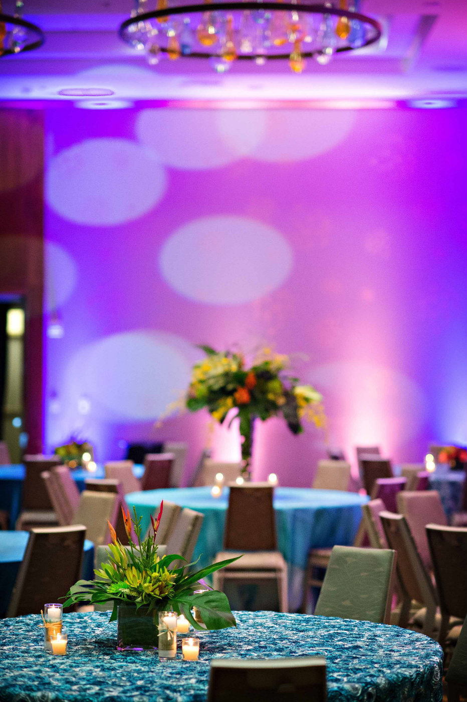 tropical centerpieces on turquoise linens for corporate party