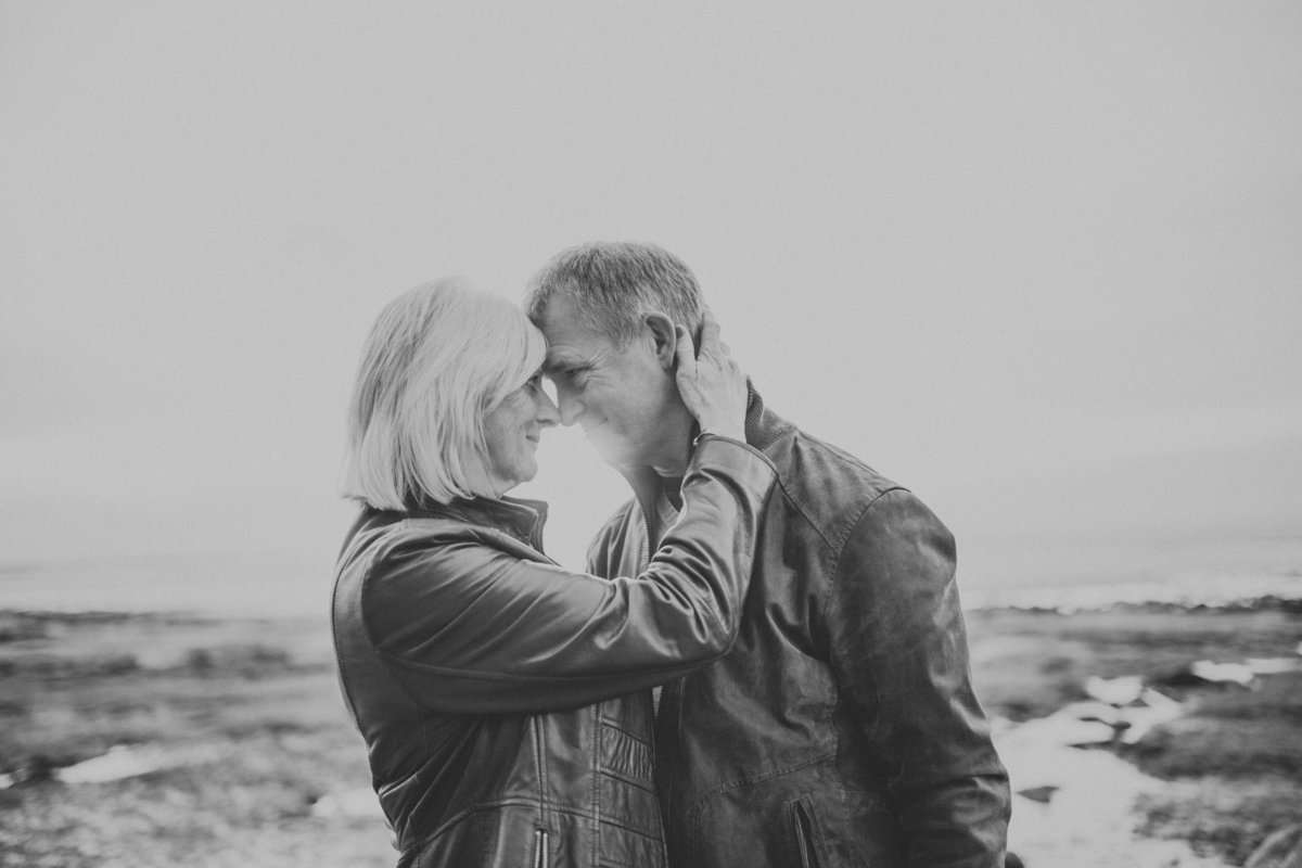 Older engaged couple in leather jackets hugging on beach in Morecambe Bay by Lancaster Wedding Photographer Jono Symonds