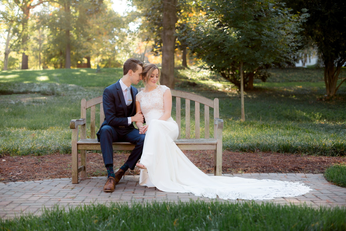 Couple poses on bench for wedding photography at Agnes Scott