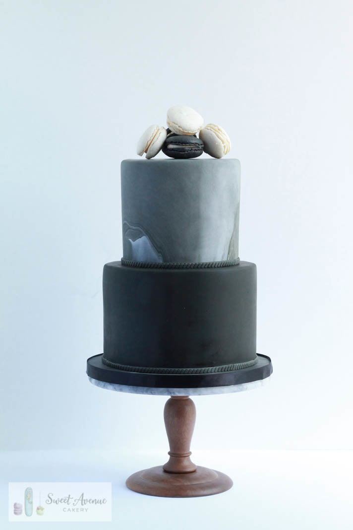 minimal, simple black wedding cake with macaron topper