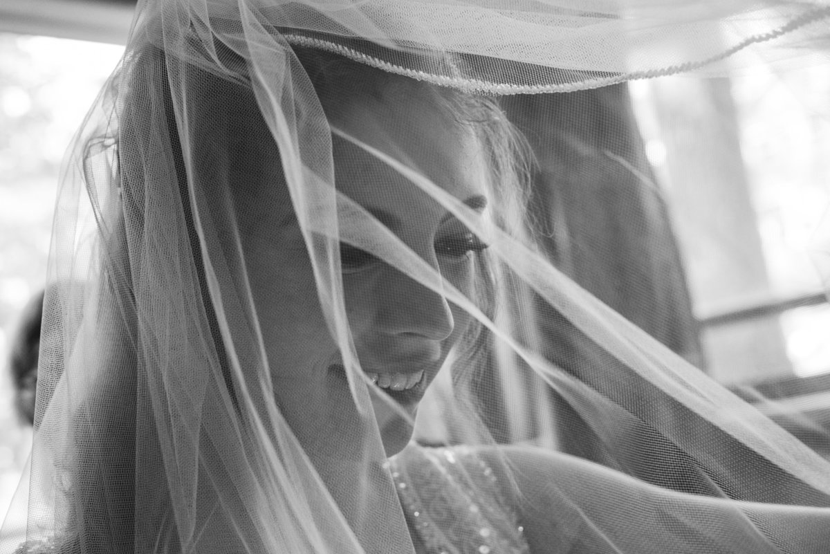black and white of bride with veil over her face