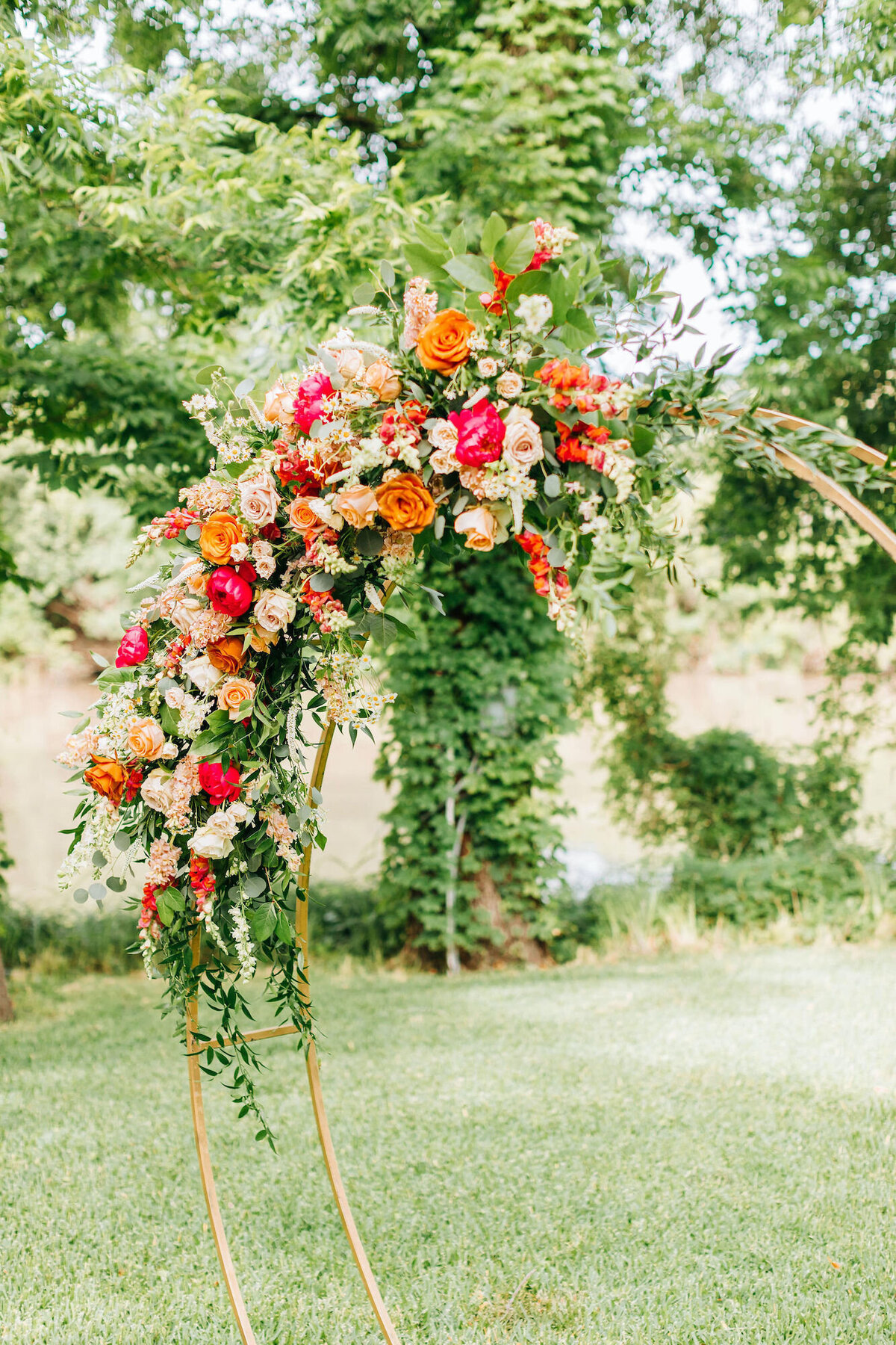Orange and hot pink florals on ceremony circle arch