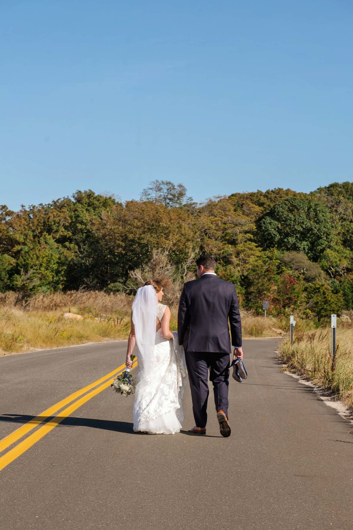 Bride and groom walking down the road at The Ram's Head Inn