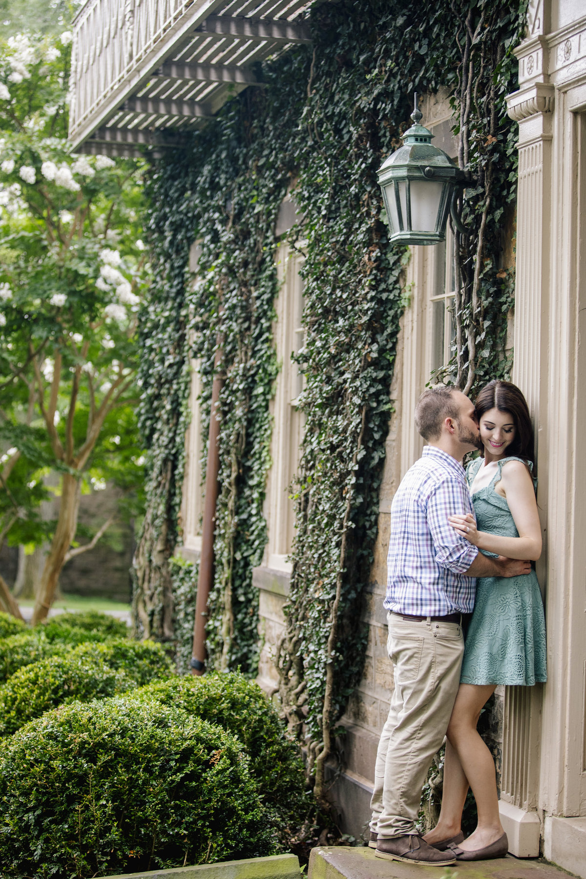 engaged couple kiss by ivy building at princeton university