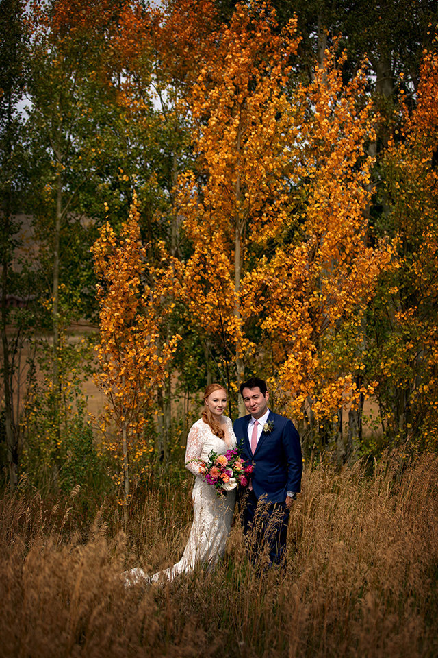 Granby-Colorado-Strawberry-Creek-Ranch-Wedding-Fire-on-the-Mountain-Wedding-Pops-of-Color-Fire-hot-colors-golden-aspen-tree-with-couple