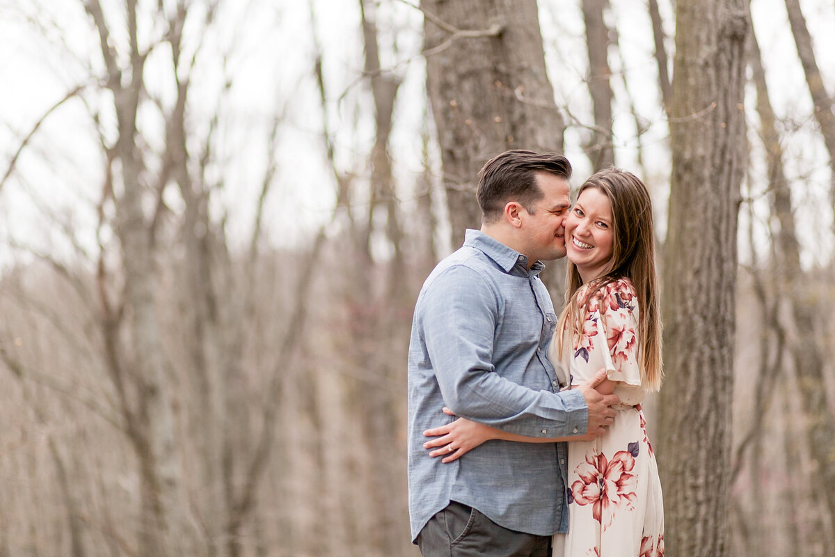 Engagement  Session with floral maxi dress  couple kissing at Greensfelder County Park in St. Louis by Amy Britton Photography Photographer in St. Louis
