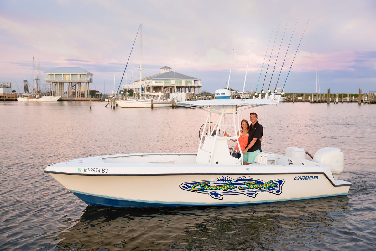 couple on boat for engagement session in pass christian ms